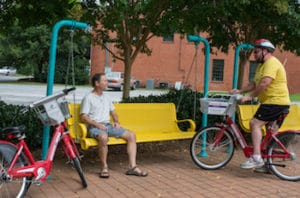 two cyclists chatting at a public bench